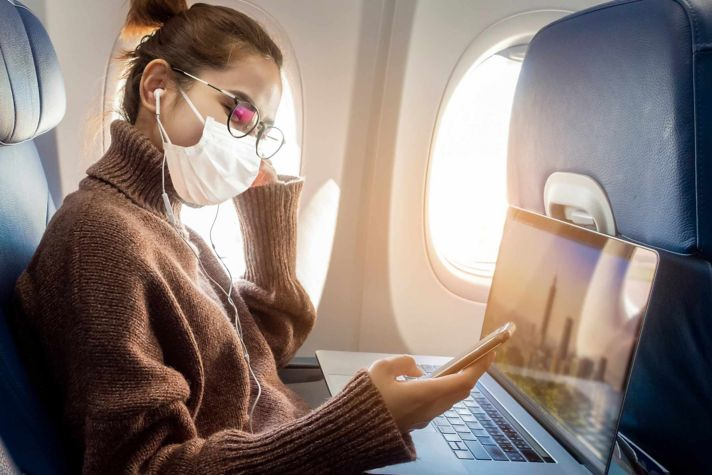 Woman on plane with mask and wi-fi