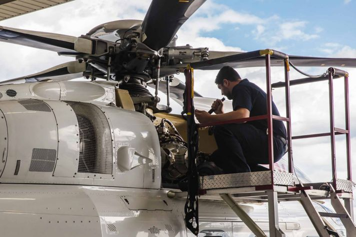 Technician performing maintenance on Helicopter