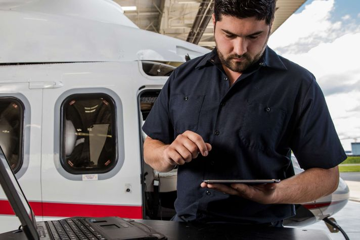 Technician using iPad on Helicopter