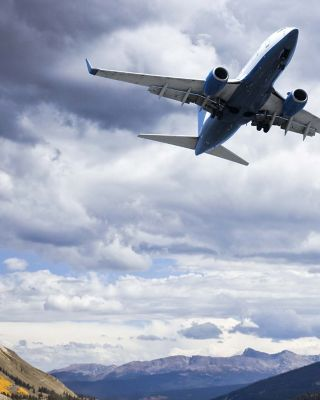 Airplane on the cloudy sky over hills
