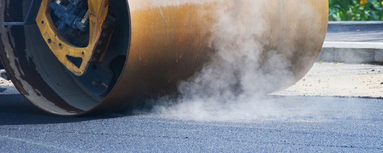 Steamroller compacting fresh layer of asphalt