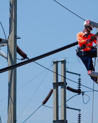 Electricians are climbing on electric poles to install and repair power lines.