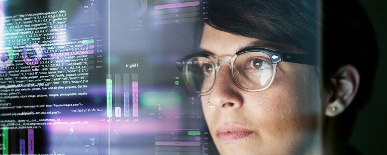 woman looking at data on monitors