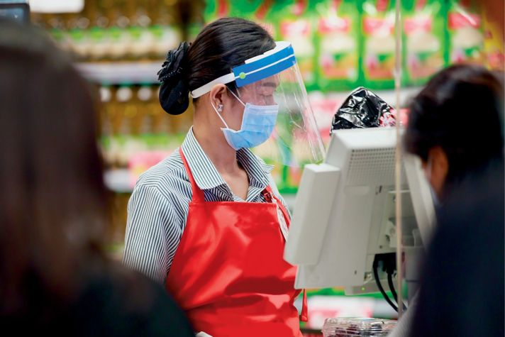 retail checkout assistant wearing safety equipment