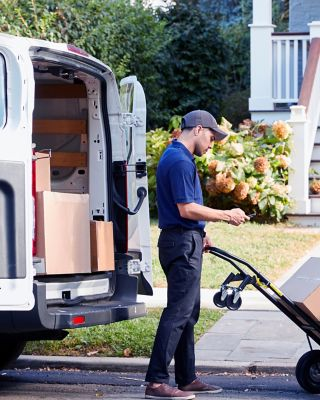 Courier delivering a package in front of a house