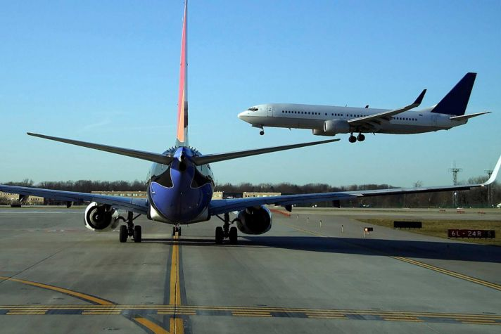 airliner landing while another waits to takeoff